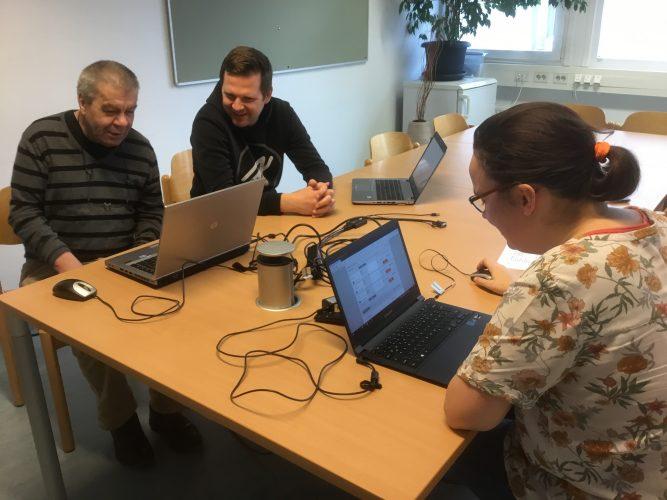 zwei leerforscher sitzen sich mit ihren Laptops an einem Tisch gegenüber , neben einen der peer forscher sitzt ein Beobachte