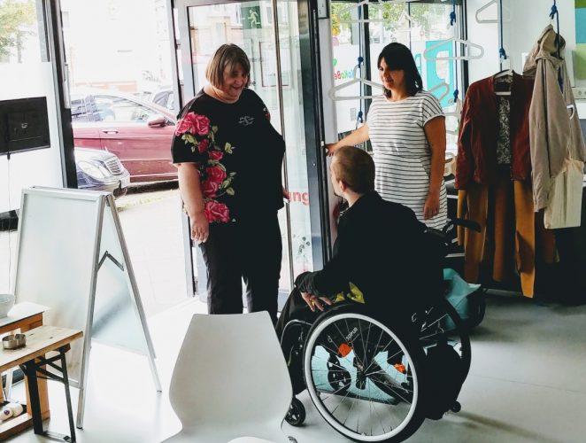 Drei Personen - zwei Frauen und ein Mann im Rollstuhl - stehen im PIKSL Eingangsbereich. Der Mann begrüßt die Frau, die durch die Tür hineinkommt.