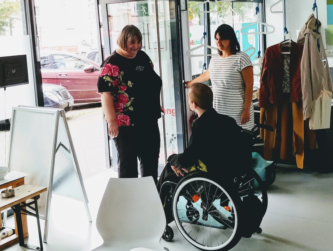Three people - two women and a man in a wheelchair - are standing in the PIKSL entrance area. The man greets the woman entering through the door.