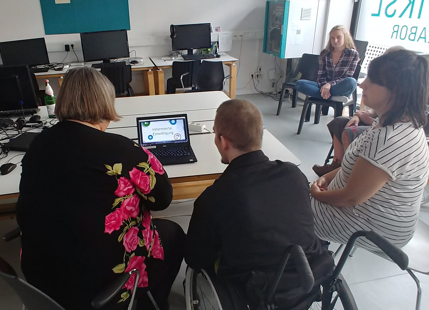 Monika and Dominik sit at a table in front of a laptop. A video of the Informed Consent is opened on the laptop.
