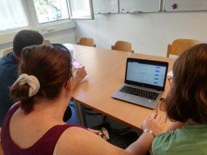 Zwei Frauen und ein Mann sitzen vor einem Laptop - sie schauen auf den Bildschirm.