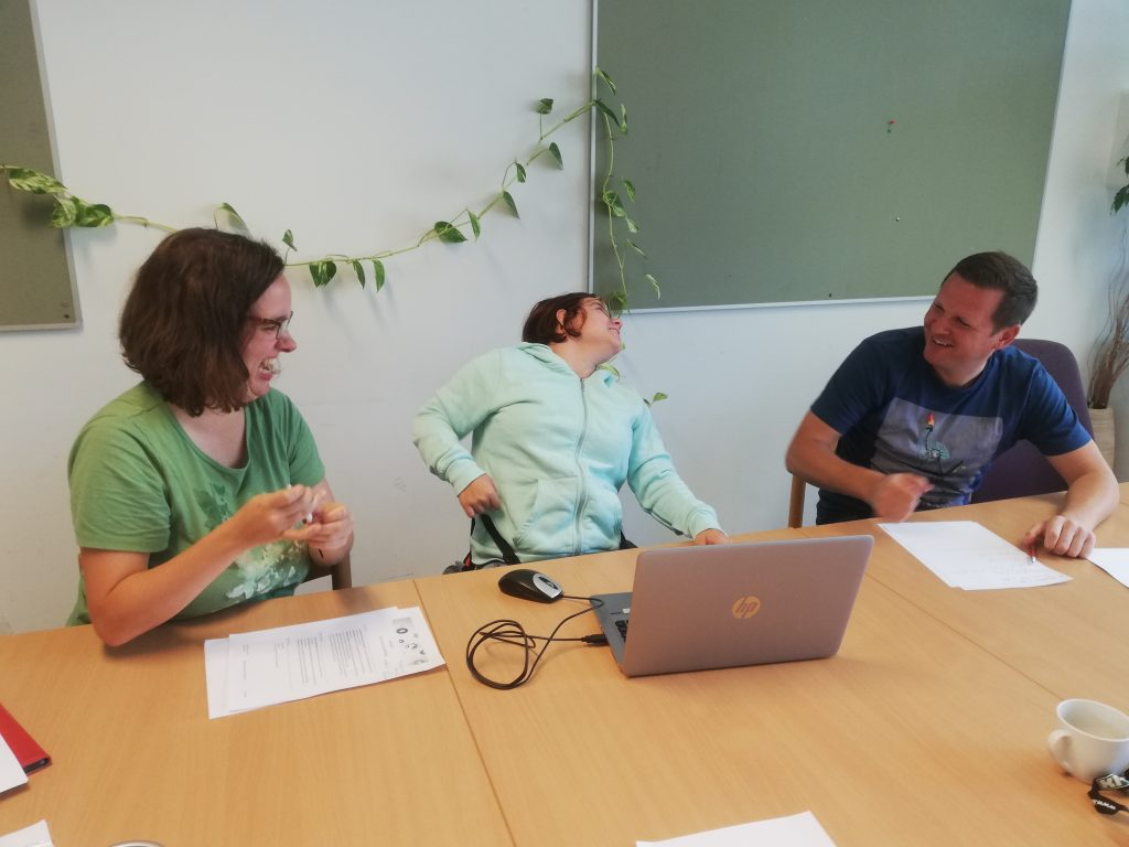Two women and a man sit together at a laptop and laugh.