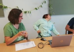 Two female easy reading members sit laughing at the table