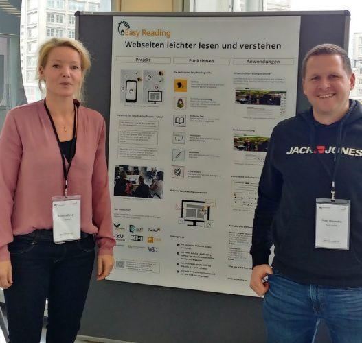 Eine Frau und ein Mann stehen am Easy Reading Stand vor einem Poster