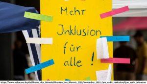 Ein gelbes Blatt Papier mit den Worten 'Mehr Inklusion für alle' mit buntem Tape an eine Scheibe geheftet