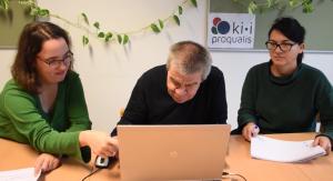 Zwei Frauen und ein Mann sitzen vor einem Laptop.