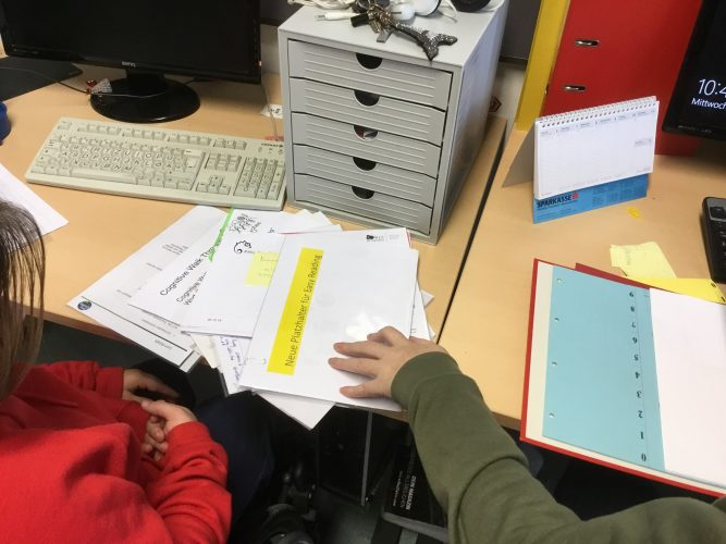 Two women sit at their desks and sort documents