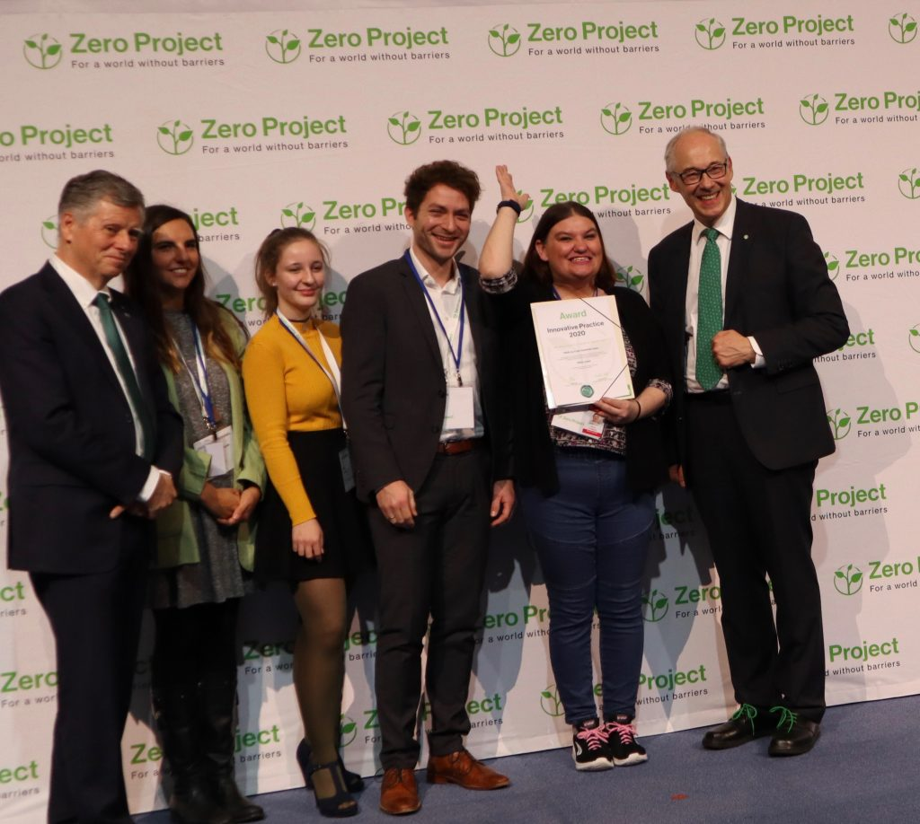 Three men and three women stand side by side and smile into the camera. One of the women is holding the award certificate in her hand. In the background is a wall with Zero Project logos.