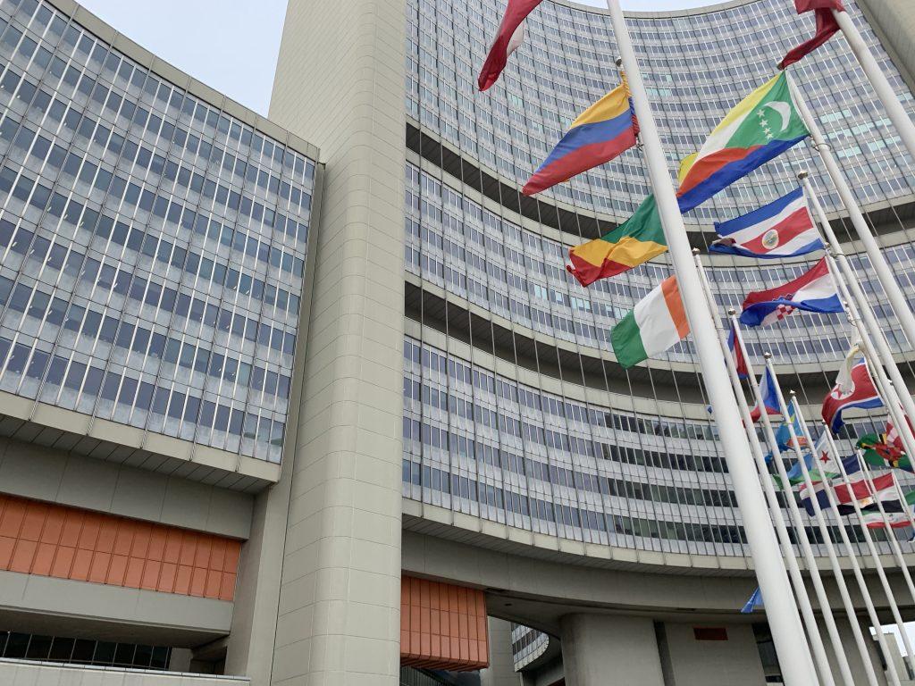 Das Gebäude der Vereinten Nationen von Außen. Die verschiedenen Länderflaggen der UN Mitglieder wehen im Wind.