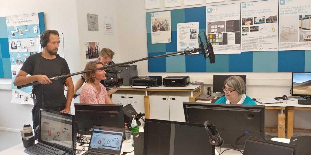 Kamerateam filmt eine Frau, die vor einem Computer sitzt